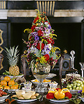 Dining table dressed with dessert setting for 1825 in the Speakers Parlour. Elaborate flower arrangement surrounded by dishes of fresh fruit, decanter, nuts.