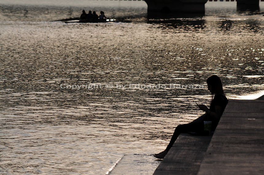 Tempe, Arizona. The silhouette of a young woman is formed by sunset light reflecting on the waters of Tempe Town Lake. The silhouette of a group kayaking on the lake is also seen in the background near a bridge. Photo by Eduardo Barraza © 2015