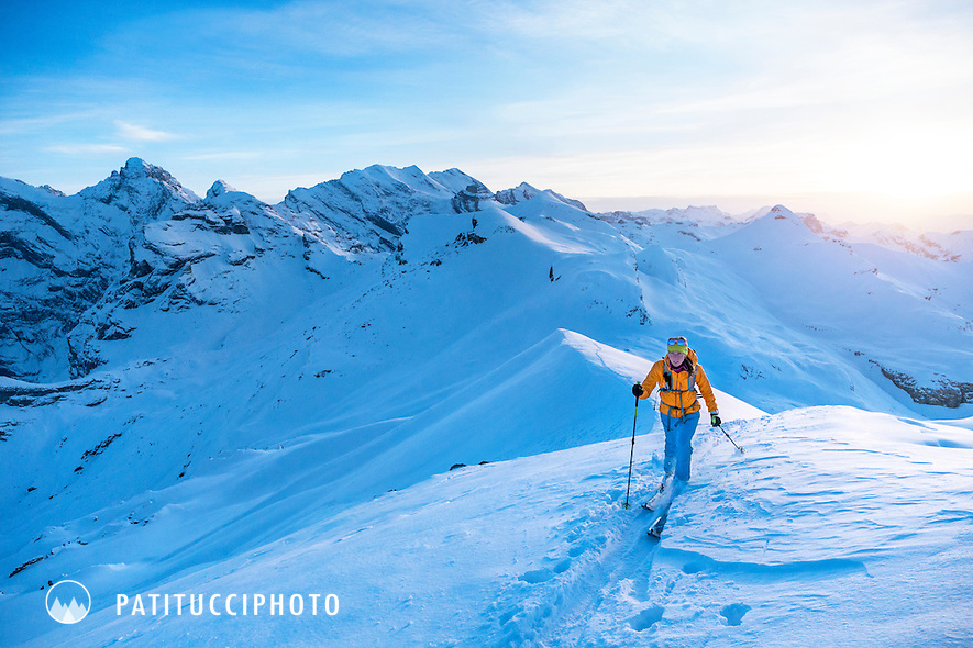 A woman ski touring at sunset in the Jungfrau Region of Switzerland