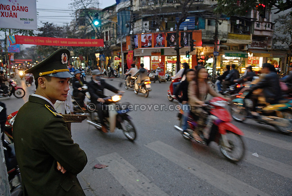 Asia, Vietnam, Hanoi. Hanoi old quarter. Official keeping an eye on the traffic flow.