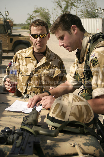 Two Royal Engineers discuss the handing over of local Iraqi engineering projects at a base in Basrah city.