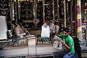 A small jewellery store owner reads the paper while other carry on work in their store in Dariba Kalan, Old Delhi, India. Photo: Sanjit Das/Panos Pictures