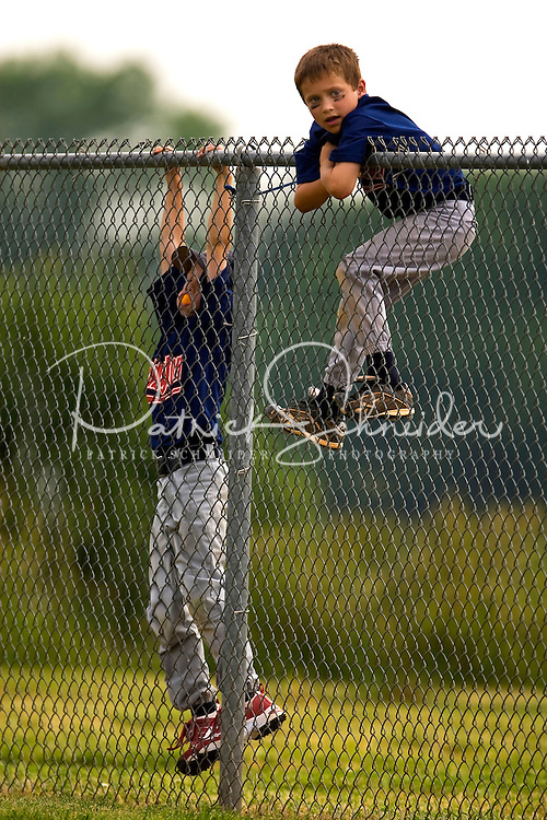 Two young baseball players climb on a fence to get a better view of the game.