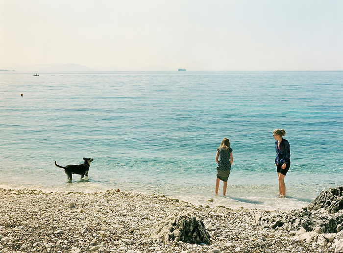 Mother,daughter and dog paddle in the sea at the beach in Nissaki, Corfu. Greece 2007.