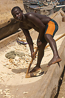 Carving a dugout pirogue, Tema, West Africa..Photograph by Peter E. Randall
