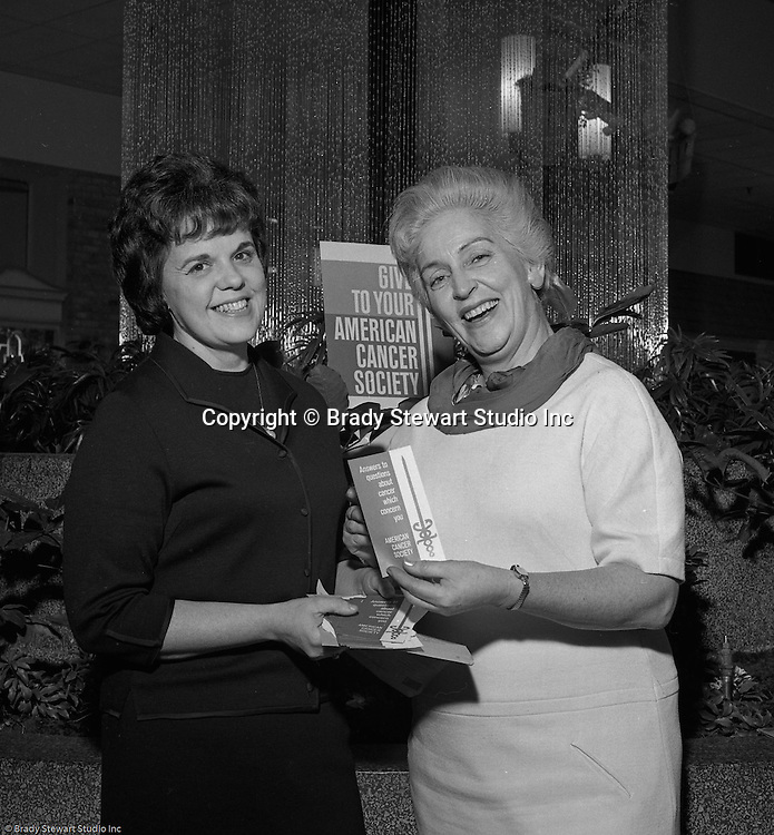 Pittsburgh PA: Volunteers handing out literature at the American Cancer Society Benefit at the new Allegheny Center Mall on the North Side of Pittsburgh - 1966.  The Daniell Sapp and Boorn agency put on the event to benefit the American Cancer Society and the new Allegheny Center Mall.  The mall recently opened and extra publicity is always a good thing.  Daniell Sapp and Boorn which opened in 1962, was active in helping good causes which indirectly promoted their insurance services. During the 1950's and 1960's local corporations and companies were very active in supporting non-profit and charitable organizations.