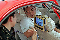 A salesman, right, introduce to a man the latest Aigo portable DVD player inside a car during a computer exhibition in Beijing, China. 08