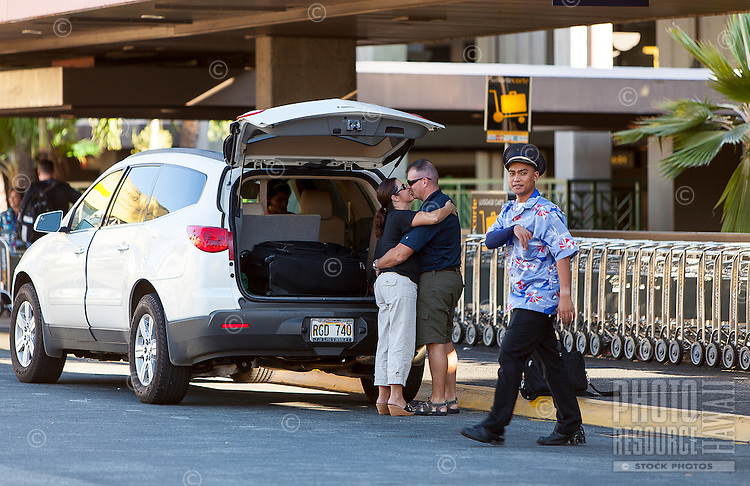 Caucasian couple kissing goodbye near their car with luggage before departure at the Honolulu International Airport, O'ahu