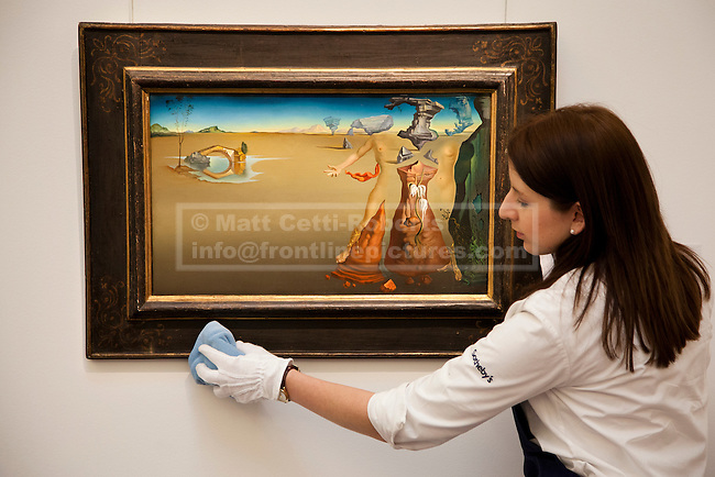 01/02/2012. LONDON, UK. A member of Sotherby's staff cleans 'Oasis' by Salvador Dali, ahead of an auction of Impressionist and Modern Art held on the 8th of February 2012. The piece is estimated to raise £4,000,000-6,000,000. Photo credit: Matt Cetti-Roberts