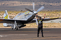 Ground crew member guides the P-51 Mustang air racer Precious Metal after a race during the 2011 Reno National Championship Air Races