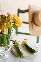 Courgettes with their bright yellow flowers are coupled with yellow roses to create an unusual flower arrangement