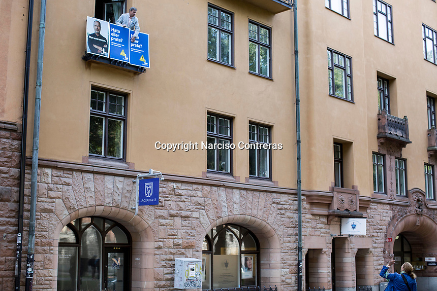 August 25, 2018: A voter for the Liberal party hangs out political advertising from his apartment balcony during a demonstration of the neo Nazi Nordic Resistance Movement NRM (Nordiska motståndsrörelsen) at the Kungsholmstorg square in Stockholm, Sweden. An estimate of 200 supporters of the neo-Nazi organisation held a six-hour rally guarded by a strong police deployment.