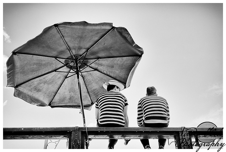 Two gondoliers sitting on Accademia Bridge, Venice, Italy.