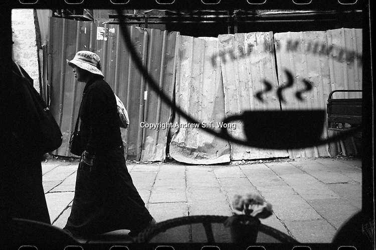 Tibetan pilgrims walks past an Italian cafe at an old alleyway in Lhasa, Tibet,  September 2016.