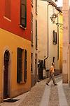 Man walking down a narrow street in Cernobbio, Italy on Lake Como.