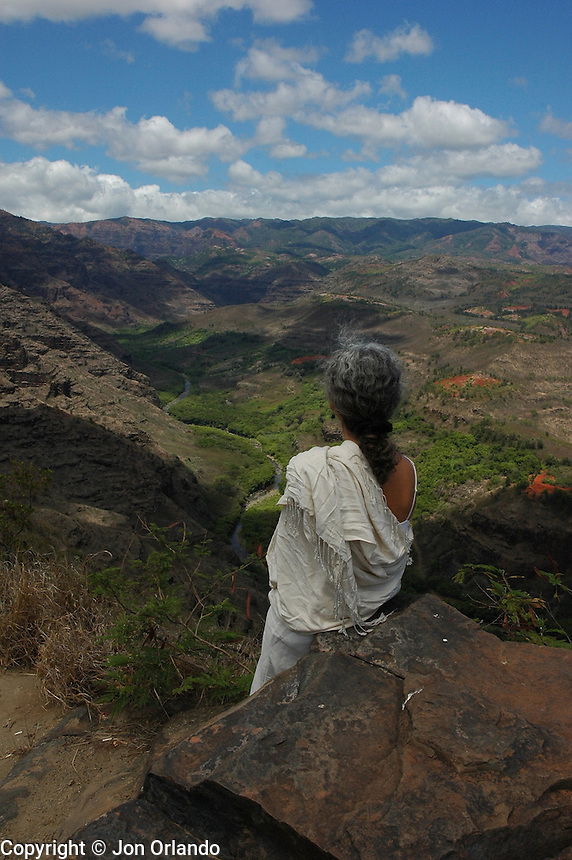 A woman overlooking a canyon on the island of Kaui, Hawaii.  Shot on location for Idanha Films.
