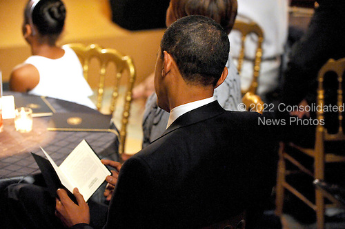 "Washington, D.C. - May 12, 2009 -- United States President Barack Obama looks over the program as he and first lady Michelle Obama host ""An Evening of Poetry, Music and the Spoken Word in the East Room of the White House in Washington, DC on Tuesday, May 12, 2009..Credit: Ron Sachs / Pool via CNP"