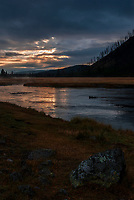 The sun tries to squeeze through the clouds at sunrise over the Madison River in Yellowstone National Park, Wyoming