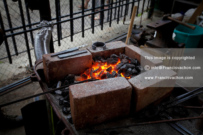 A blacksmith works a piece of iron in Detroit Eastern Farmers market in Detroit (Mi) Saturday June 8, 2013. The largest open-air flowerbed market in the United States, the Eastern Market is a historic commercial district in Detroit, Michigan.