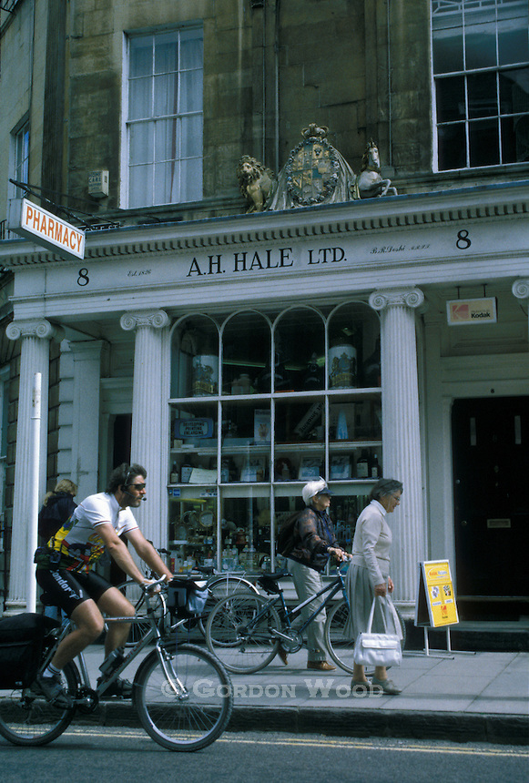 Bike Courier cyclist and pedestrian outside pharmacy Bath England