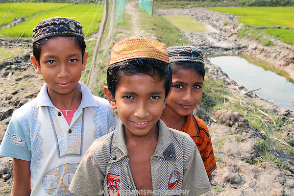Built in the 15th century, the red brick mosques scattered around Bagerhat are still in use by local people. These three boys were on their way to prayers at Chunakola Mosque, situated amongst rice paddies in Bagerhat.