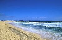 Couple walking along empty sandy beachs with Atlantic waves pounding shore, Corralejo, Fuerteventura,Canary Islands.