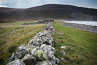 Old stone wall leads towards Burnmouth Bothy, Rackwick Bay, Hoy, Orkney, Scotland