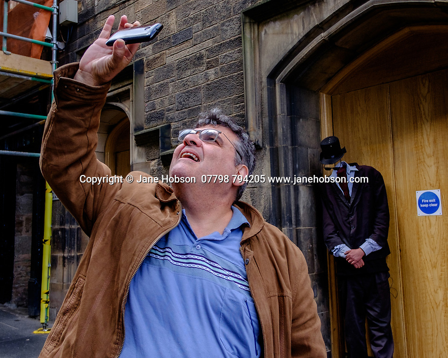 Edinburgh, UK. 15.04.2017. A man takes a selfie, with Mr Nobody in the background, on the Royal Mile. Photograph © Jane Hobson.