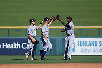 Scottsdale Scorpions outfielders Troy Montgomery (4), Kevin Kaczmarski (17), and Estevan Florial (19) congratulate each other after an Arizona Fall League game against the Mesa Solar Sox on October 24, 2017 at Sloan Park in Mesa, Arizona. The Scorpions defeated the Solar Sox 3-1. (Zachary Lucy/Four Seam Images)