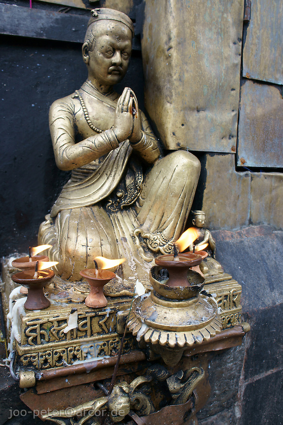 metal figure in praying position at buddhist temple Swayambhu in Kathmandu, Nepal, September 2011