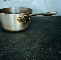 An old aluminium saucepan is abandoned on a slate worktop