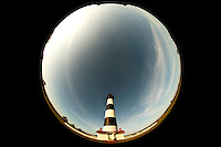 The striking black-and-white-striped Bodie Island Lighthouse located on Bodie Island on North Carolina's Outer Banks. Photo taken using an 8 mm circular fish eye lens, which shows a 180-degree view of the lighthouse and sky. The light house, built in 1872, stands 156 feet tall and is located on the Roanoke Sound side of the first island that is part of the Cape Hatteras National Seashore. The lighthouse is just south of Nag's Head, a few miles before Oregon Inlet. The conical-shaped lighthouse has white and black bands with a black lantern house. Charlotte NC photographer Patrick Schneider has extensive photo collections of the following lighthouses: Bodie Island Lighthouse, Bald Head Island Lighthouse, Cape Fear Lighthouse, Cape Hatteras Lighthouse, Cape Lookout Lighthouse, Currituck Beach Lighthouse, Diamond Shoal Lighthouse, Federal Point Lighthouse, Oak Island Lighthouse, and Ocracoke Lighthouse on Ocracoke Island.
