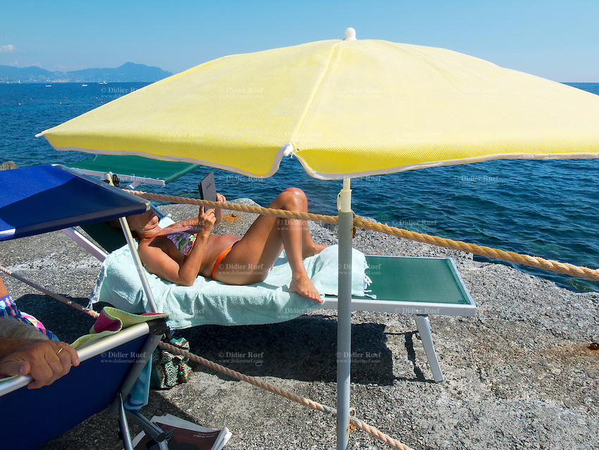 Italy. Liguria Province. Genova. Nuovo Lido beach resort. A woman is sunbathing and reads a book on her Amazon Kindle device. Yellow beach umbrella on the rocks above the Mediterranean sea. The Amazon Kindle is a series of e-book readers designed and marketed by Amazon.com. Amazon Kindle devices enable users to shop for, download, browse, and read e-books, newspapers, magazines, blogs, and other digital media via wireless networking. The hardware platform, developed by Amazon.com subsidiary Lab126, began as a single device and now comprises a range of devices – most using an E Ink electronic paper display capable of rendering 16 tones to simulate reading on paper while minimizing power consumption. 18.08.13 © 2013 Didier Ruef