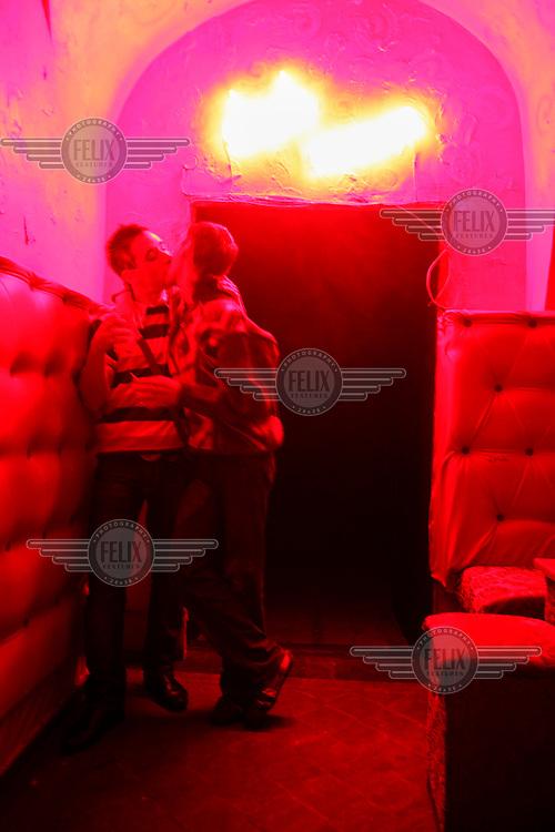 To men kissing in a gay nightclub.