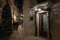 "Italy. Apulia Region. Locorotondo. Christmas decoration. A group of elderly men holds arms and walks together in the tiny streets at night time. Locorotondo is a town and comune with a population of about 14,000. The city is known for its circular structure which is now a historical center, from which derives its name, which means ""Round place"". Apulia (Puglia) is a region in Southern Italy. 5.12.18  © 2018 Didier Ruef"