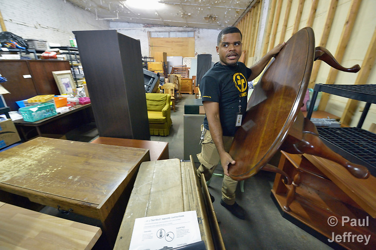 Luis Ortiz carries a table in a Church World Service warehouse in Lancaster, Pennsylvania. He is loading a truck with goods to furnish the apartment of a refugee family about to arrive in the United States.<br /> <br /> Photo by Paul Jeffrey for Church World Service.
