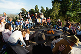 USA, Wyoming, Encampment, guests at a dude ranch sit around a campfire and listen to a man play the guitar and sing country western songs, Abara Ranch