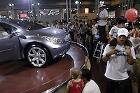 Visitors look at cars from GM at the Auto China 2004 exhibition in Beijing, China. SGM is a joint-venture between General Motors and the Shanghai Automotive Industry Corporation also known as SAIC..