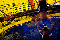Young Colombian boys practise an acrobatics act at the Circo Anny, a family run circus wandering the Amazon region of Ecuador, 4 July 2010. The Circo Anny circus belongs to the old-fashioned traveling circuses with a usual mixture of acrobat, clown and comic acts. Due to the general loss of popularity caused by modern forms of entertainment such as movies, TV shows or internet, these small family enterprises balance on the edge of survival. Circuses were pushed away and now they have to set up their shows in more remote villages. The circus art and culture is slowly dying.