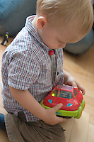 Toddler examining remote car. Balucki District Lodz Central Poland