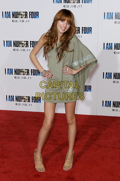 "BELLA THORNE.World premiere of DreamWorks Pictures' ""I Am Number Four"" at the Village Theatre in Westwood. Los Angeles, CA, USA. February 9th, 2011.full length grey gray one shoulder dress hands on hips red nail varnish polish ankle open toe shoes boots .CAP/CEL .©CelPh/Capital Pictures"