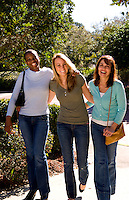 Three friends girlfriends walking outdoor in sunshine with mixed ethnics of white and black African American