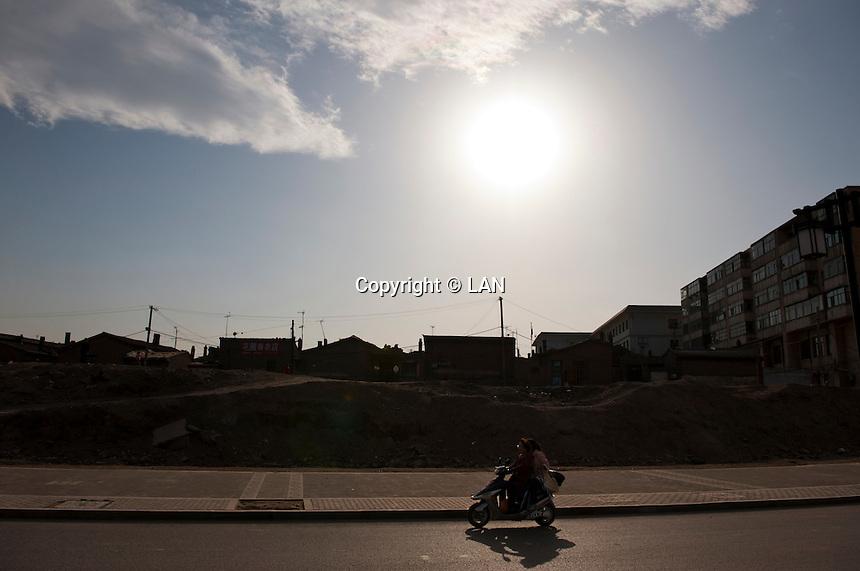 Daytime horizontal view of a man and woman riding a scooter on Yu He Xi Lu in front of a siheyuan lot on a hútòng in the old part of Dàtóng Shì Chéng Qū in Shānxī Province, China  © LAN