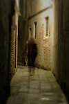 A shadowy figure stands under a street light in a dark Venice alley.