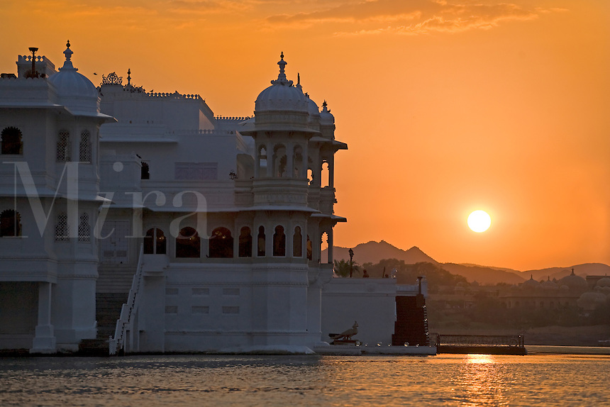 Sunset behind the LAKE PALACE HOTEL on JAGNIWAS ISLAND in LAKE PICHOLA was built by Maharaja Jagat Singh ll in 1754 - UDAIPUR, RAJASTHAN, INDIA