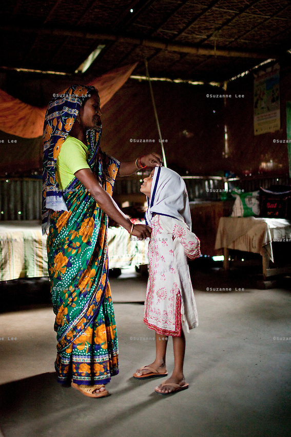 Shahida Begum, 35, dresses her daughter, Mahfuza Akhter (5), in her hut in Palashbari Villlage, Taragonj, Rangpur, Bangladesh on 18th September 2011, after a regular day of work as a saleswoman earning 3500 - 5000 Bangladeshi Taka per month. She is one of many rural Bangladeshi women trained by NGO CARE Bangladesh as part of their project on empowering women in this traditionally patriarchal society. Named 'Aparajitas', which means 'women who never accept defeat', these women are trained to sell products in their villages and others around them from door-to-door, bringing global products from brands such as BATA, Unilever and GDFL to the most remote of villages, and bringing social and financial empowerment to themselves.  Photo by Suzanne Lee for The Guardian
