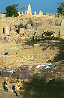 Mali. Province of Mopti. Dourou. Dogon land. Near the Bandiagara cliff. Village life. Women carry buckets on their heads to fetch water. Clothes washed earlier in the day are drying on the rocks in the sun. Traditional houses with millet, sorghum, maze loft. The white mosque is on the top of the hill.  © 2003 Didier Ruef