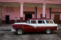 red-white oldtimer in front of a pink buidling with columns, street scene in Havana, Cuba