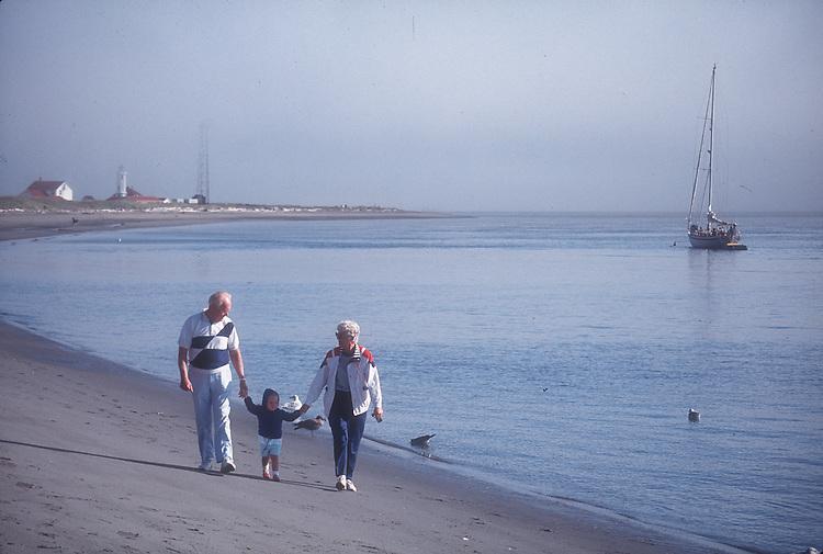 Beach, Grandparents walking grandchild, Fort Worden, Point Wilson, Port Townsend, Puget Sound, Washington State, U.S.A. Washington State Parks,