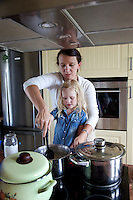 Polish mom helping daughter age 4 cook and stir at stove. Zawady Central Poland